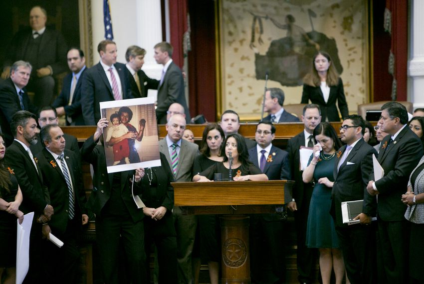 "State Rep. Veronica Neave, D-Dallas, gives an emotional speech as a picture of her father is held up during the debate on SB4 — the ""sanctuary cities"" bill — on April 26, 2017."