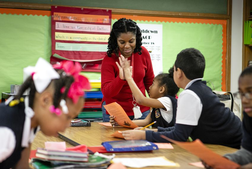 Natasha Boone high-fives a student while going over a story in class at Edward Titche Elementary School in the Pleasant Grove area of Dallas.