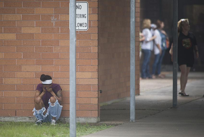 A young woman mourns after a May 18, 2018 school shooting at Santa Fe High School left multiple fatalities.