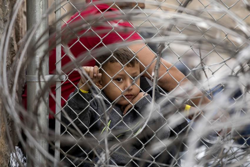 A young boy looks though fencing and razor wire inside a temporary migrant holding area under the Paso del Norte Internati...