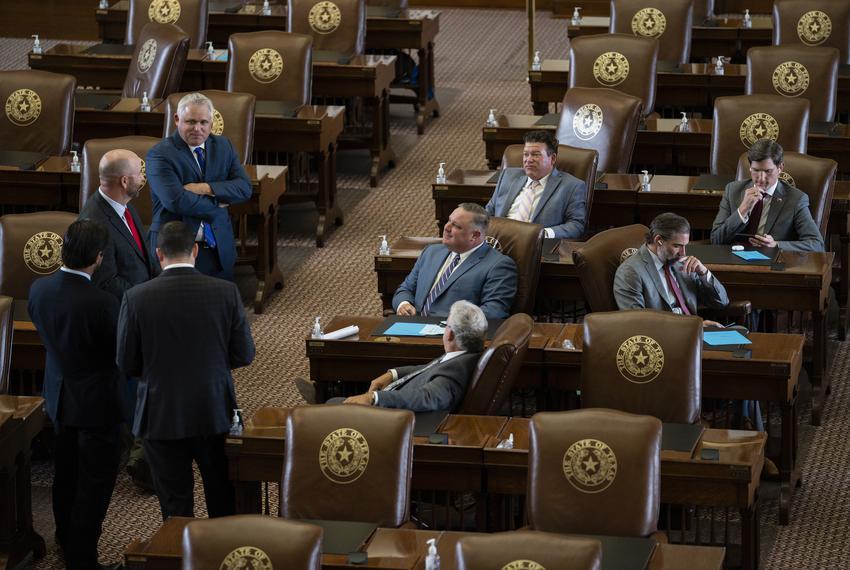 Legislators talk amongst themselves on the House floor on July 29, 2021.